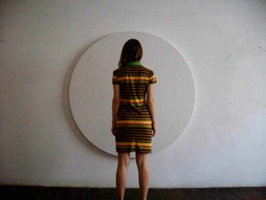 simonetta from the back wearing a striped dress in front of a white round canvas